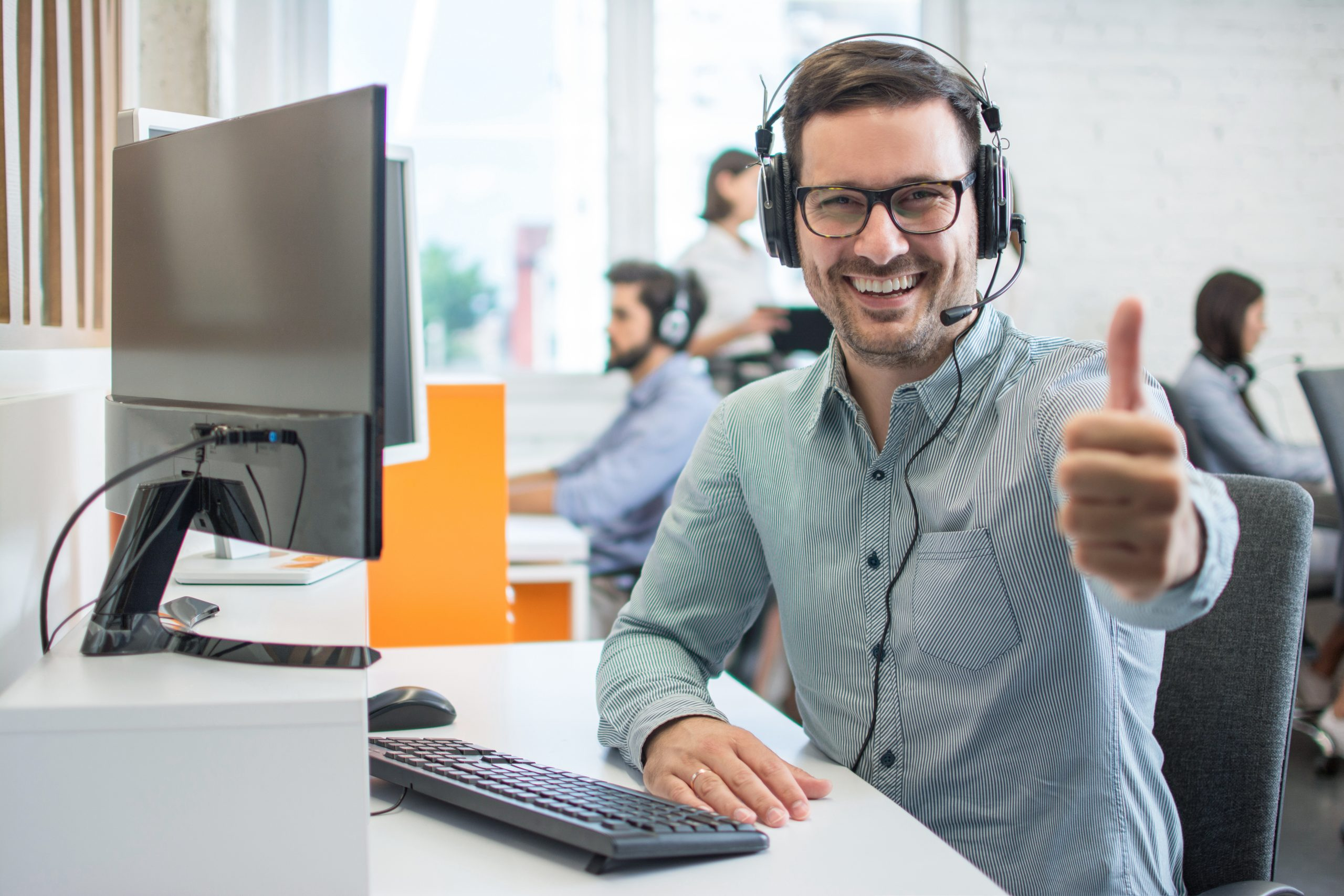 Friendly cheerful male customer support service operator man showing thumbs up in call centre.