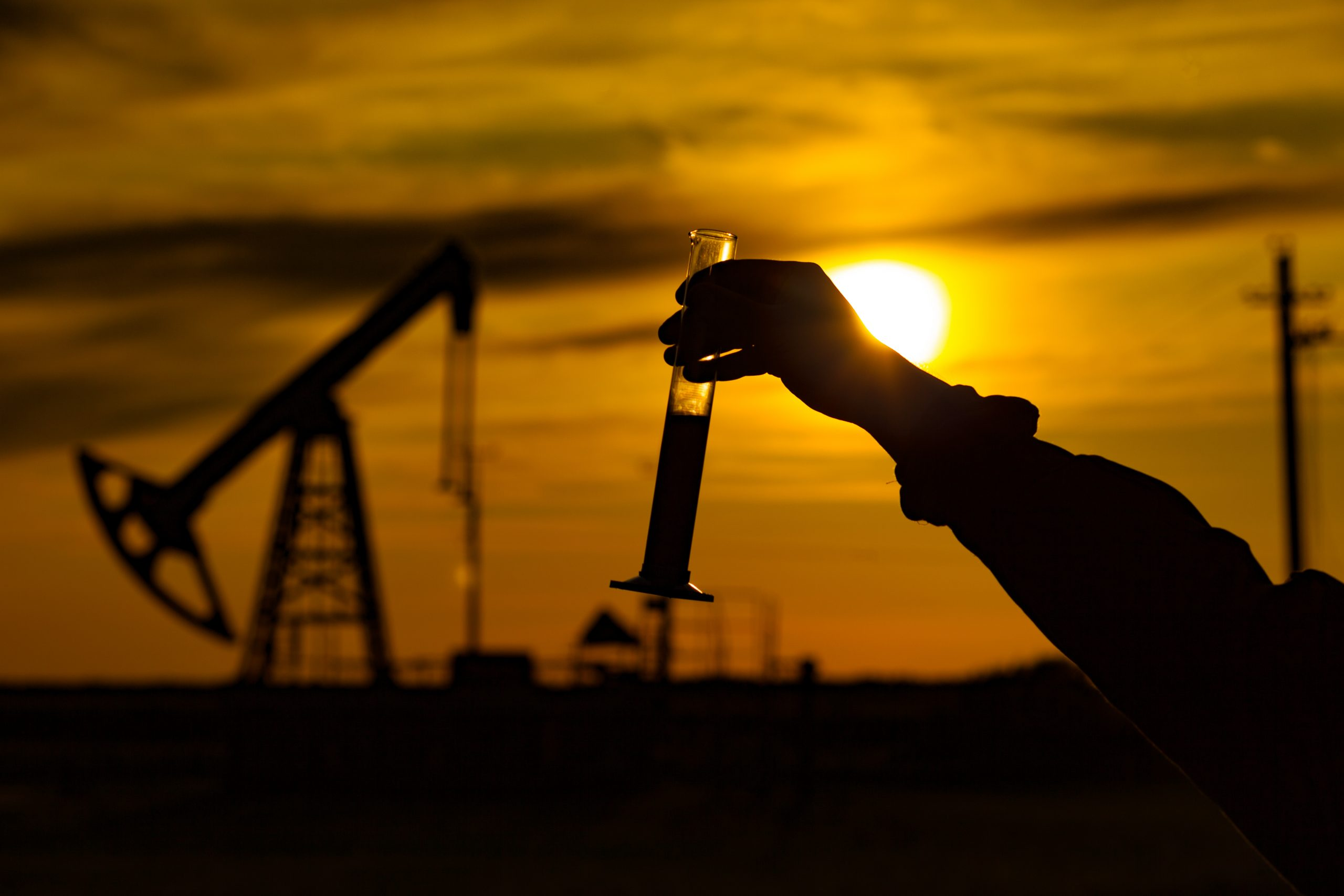 A man holding a flask of oil. Oil rigs in the background. Oil production in Russia. Sunset. Oil pumping